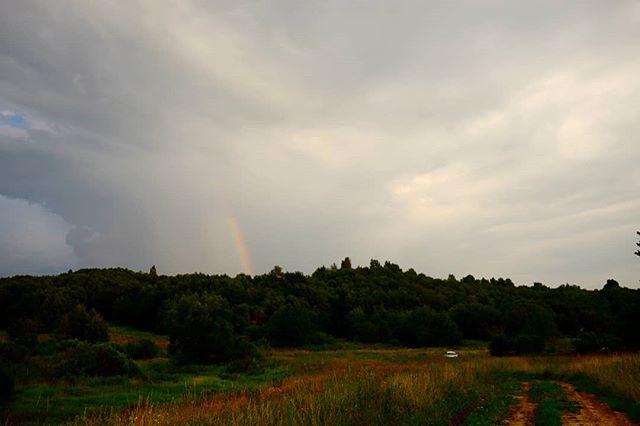 Машина в траве и радуга на небе